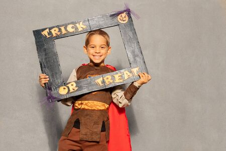 Cute beautiful little boy in costume with Halloween trick or treat frame stand over wall Standard-Bild