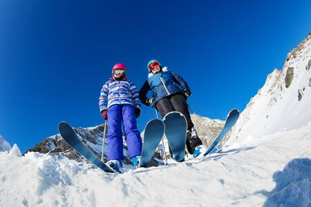 View from below of two girls stand on ski wearing helmets and masks on top of the mountain