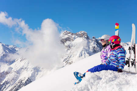 Two happy girls sit in the mountain with ski over high peaks and clouds in snow look on the valley