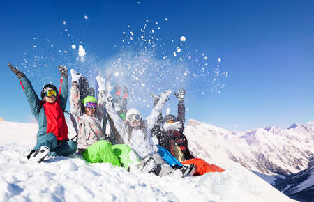 Group of young adults throw snow up in the air sitting on top of the mountain over sunny alpine peaks
