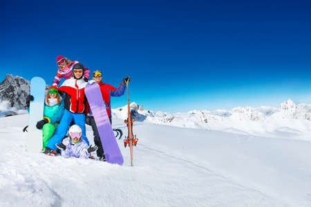 Group of young adults snowboarders pose together on top of the mountain over snow covered peaks on sunny weather on back Standard-Bild