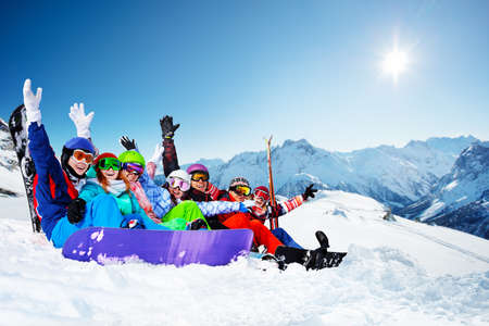 Group of happy young adults hold snowboard sit together with lifted hands waving Stockfoto