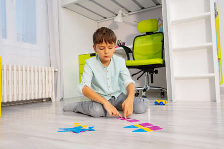 Calm boy put geometric shapes in order sitting on the floor in kids room
