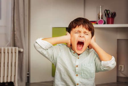 Little autistic boy with strong negative face expression closing ears and loudly screams Stock Photo
