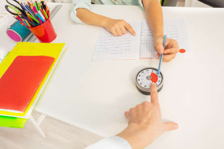 Teacher womans hand point to the lesson timer during development class exercise