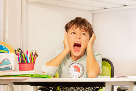 Sad crying autistic boy sitting during development therapy by the desk with lesson timer Archivio Fotografico