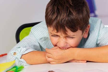 Boy with autism spectrum disorder bite hand and negative expression behavior, close portrait Archivio Fotografico