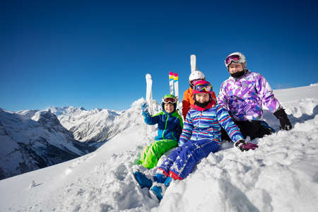 Fun group portrait of children sit together in snow over magnificent mountain range tops in Alps