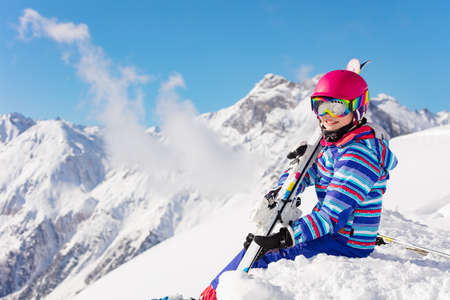 Happy young girl in bright sport outfit sit on the snow pile in the mountain over high peaks and clouds on sunny day