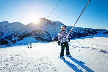 Happy teen girl lifting on the ski drag lift rope in bright sport outfit over sunset light near mountain peak