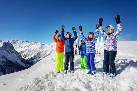 Big group of ski kids stand on snow rise hands cheerfully smiling over mountain range peaks in colorful sport outfit Banco de Imagens