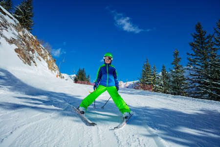 Cute 10 years old boy skier learning to ski down the slope in bright green outfit on sunny day