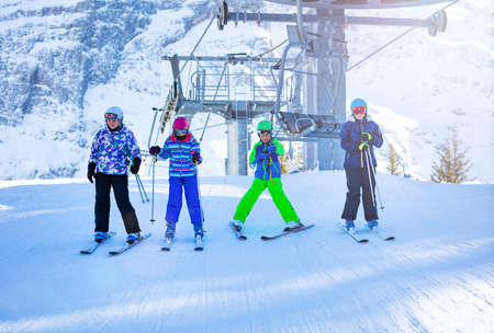 Group of four kids boy and girls ski after taking off from chairlift seat of alpine resort