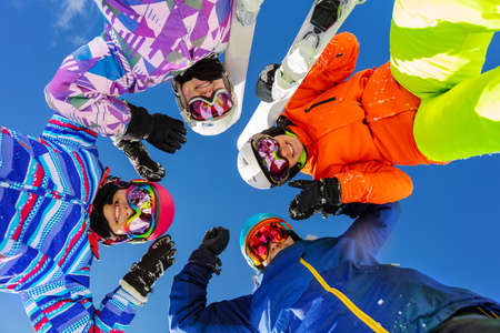 Four teenage girls look down with ski and winter sport outfit standing together smiling