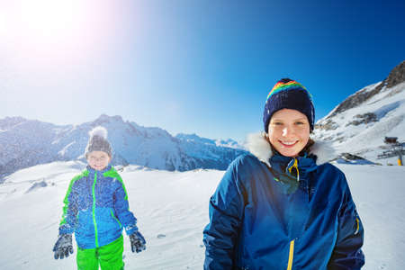 Two happy kids girl with boy have fun stand together throw snow in the air over beautiful mountain view