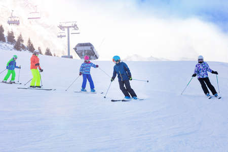 Class group of kids in ski school move one after another on Alpine slope learning Stockfoto