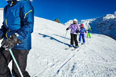 Three of kids ski on the Alpine slope as part of the school group one after another with mountains on background