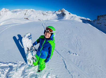 Wide mountain panorama and cute little smiling boy hold snowboard in hand aside, view from above with mask off