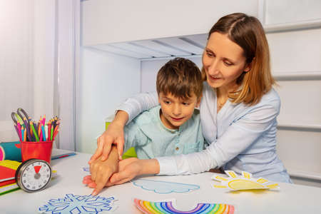 Boy with autism learn weather using cards, teacher hold hands and point to correct one Zdjęcie Seryjne