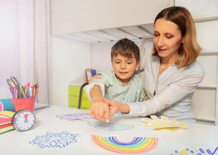 Child with autism spectrum disorder learn weather using cards, teacher hold hands and point to correct one Zdjęcie Seryjne