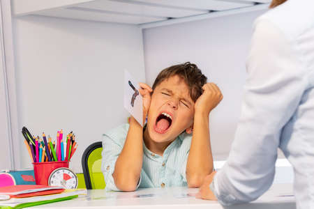 Autistic child tear hairs and scream expressing negative emotions while learning numbers sitting by teacher