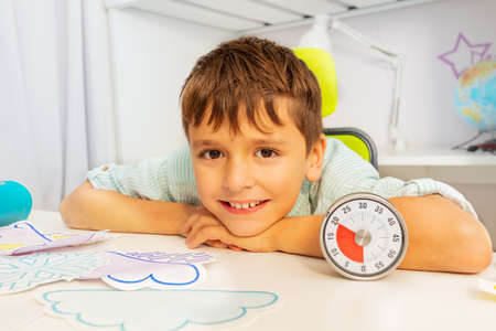 Patient happy boy during aba development therapy sitting smile to camera sit with card and lesson timer
