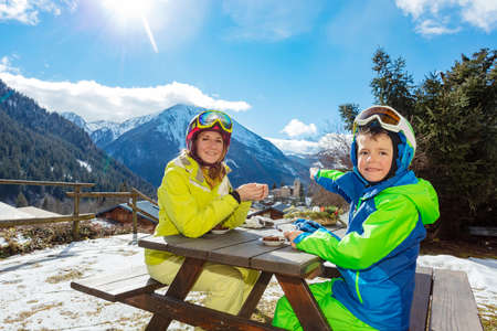 Smiling boy in ski outfit sit enjoy lunch break with mother pointing finger and discussing village below 免版税图像