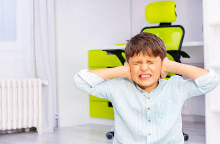 Autistic school age boy with strong negative face expression closing ears and grins teeth sitting in his room