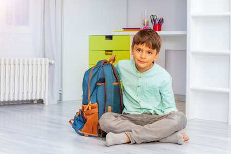 Smiling calm little boy sit in his room with positive expression holding school rucksack