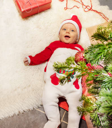Cute baby little toddler boy lay on the carpet with open mouth laughing and looking at camera under Christmas tree