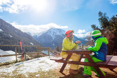 Boy in ski outfit sit and enjoy lunch break with mother looking on mountain view after skiing Reklamní fotografie