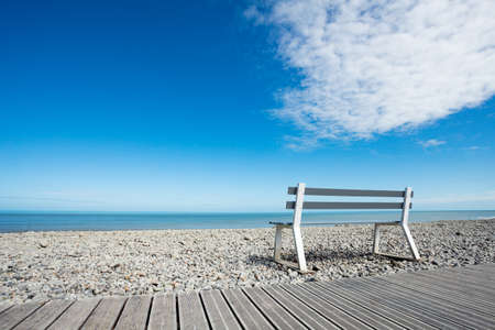 Beautiful wooden bench over clean beach and ocean background