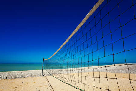 Volleyball net over sand beach and ocean view by blue sky background Reklamní fotografie