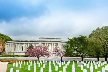 The Arlington Memorial Amphitheater over National Cemetery tombstones with blooming cherry trees, Virginia