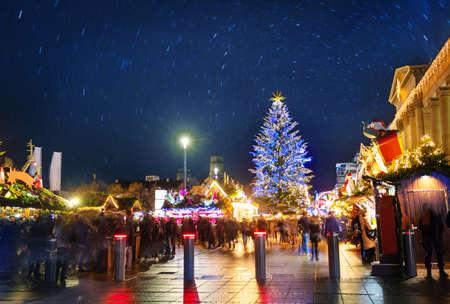 Crowds over illuminated Christmas tree and market fair on Castle square or Schlossplatz in German, Stuttgart Stock Photo