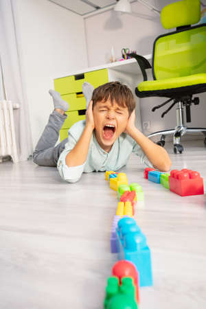 Autistic boy put toys in a row lay on the floor scream and cover ears with hands