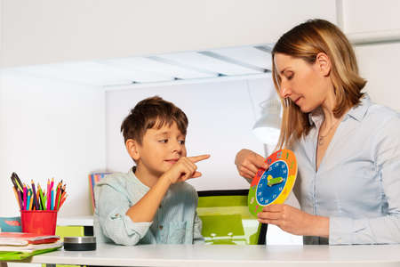 Child with autism spectrum disorder learn clock and hours, teacher during ABA therapy class