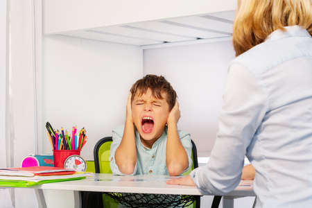 Autistic boy scream and close ears in pain during ABA development therapy sitting by the table with teacher Reklamní fotografie