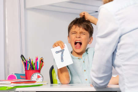 Boy with autism tear hairs and scream expressing negative emotions while learning numbers sitting by teacher, self-injury issue