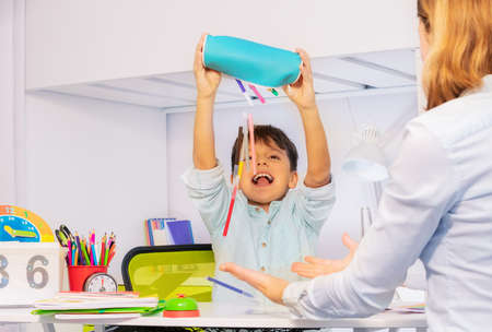 Boy with autism spectrum disorder throw pens and pencils negative expression behavior sitting near teacher