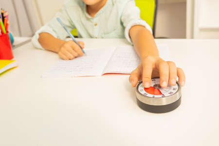Little autistic boy hold lesson timer with hand while doing writing exercise, understanding time