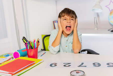 Boy with autism spectrum disorder learn numbers but scream and close ears in the class, sensory issue Reklamní fotografie