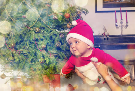 Happy little boy in hands of mother play flying in front of the Christmas tree
