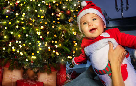 Happy little toddler baby boy in front of Christmas tree in mothers hands Reklamní fotografie
