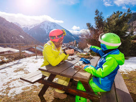 Little boy in ski outfit sit enjoy lunch break with mother pointing finger and discussing village below
