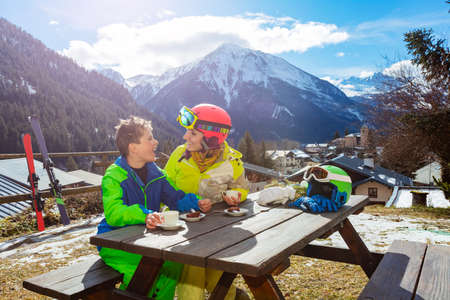 Mother look at and talk to a little boy in ski outfit sit, enjoy lunch break over mountain view after skiing