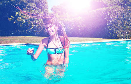 Happy dancing girl shake hair and head smiling standing in the swimming pool in the garden