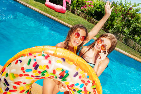 Two laughing girls with rise hands and hold inflatable buoy near swimming pool