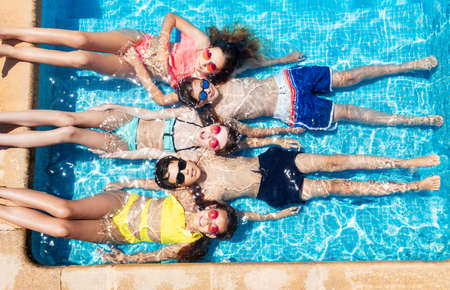 Group of boys and girls lay in a row in the swimming pool water view from above in sunglasses
