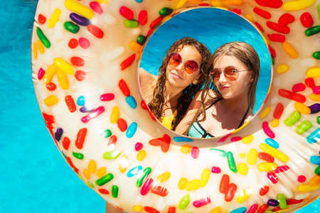 Two happy preteen girls inside the inflatable buoy smile wearing near swimming pool in sunglasses with nice smiles Stock Photo